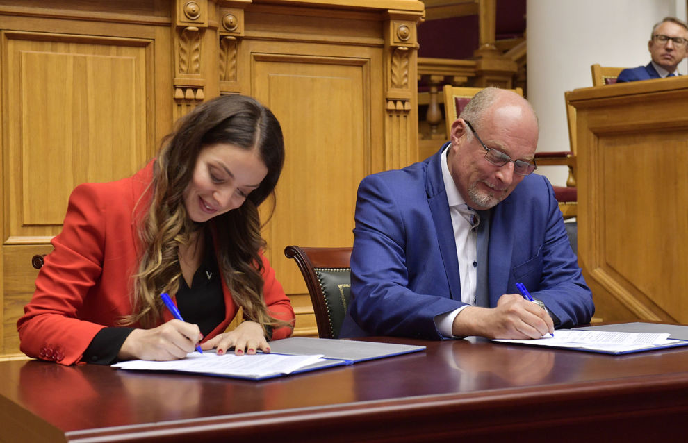"Sergei Korneyev, Deputy Head of the Federal Agency for Tourism, and Zarina Doguzova, Head of the Federal Agency for Tourism (Rostourism) sign documents during the plenary session ""Arctic tourism, unique features and development prospects"" at the Accessible Arctic forum in St. Petersburg"