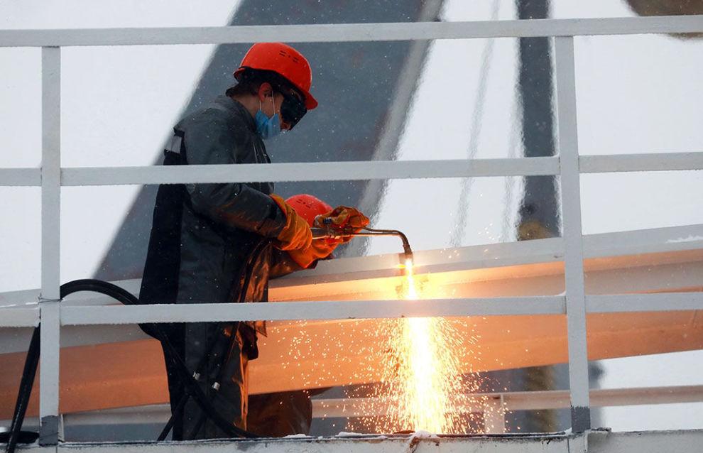 Сотрудник АО Адмиралтейские верфи режет задержник во время церемонии спуска на воду ледостойкой самодвижущейся платформы (ЛСП) Северный полюс проекта 00903 в Санкт-Петербурге