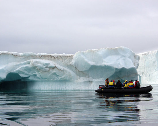 Tourists view the icebergs near Champ Island from inflatable Zodiac boats, Franz Josef Land