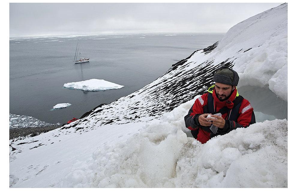 На склоне мыса Флигели зоолог Мирослав Бабушкин обследует самую северную в Евразии берлогу белого медведя