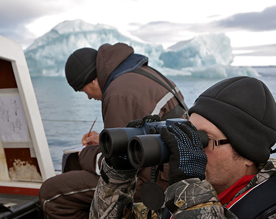 Expedition members Dmitry Moseyev and Yevgeny Kuzmin aboard the yacht monitor the island coastal zone