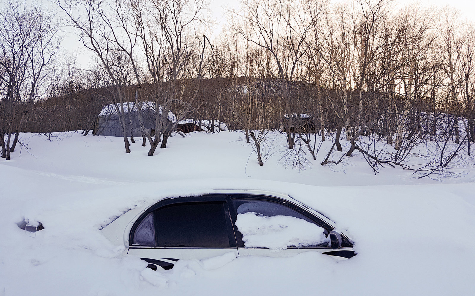 A snowed-in car in a courtyard in Petropavlovsk-Kamchatsky