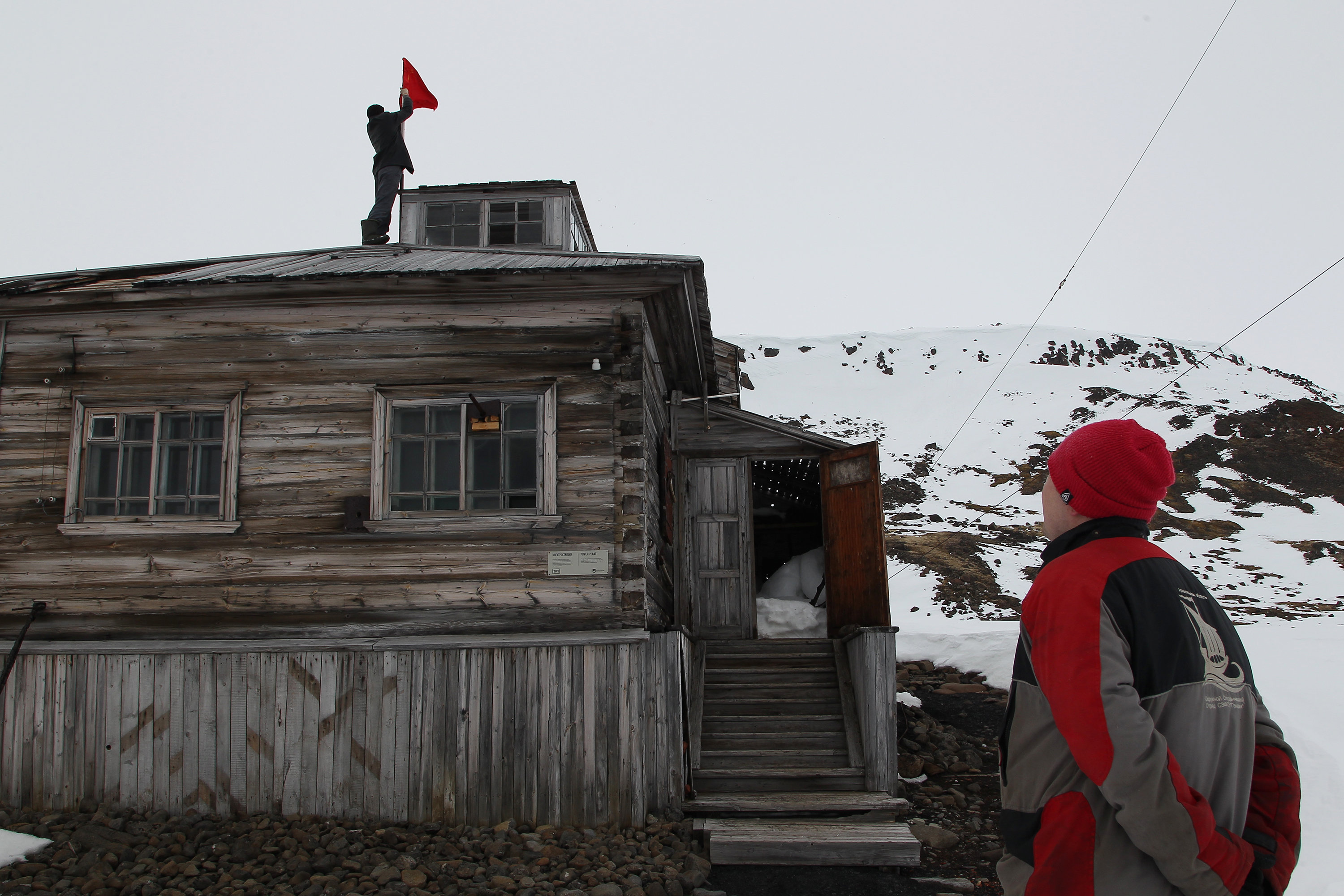 Installing a flag before the opening of the station, Franz Josef Land, Russian Arctic National Park