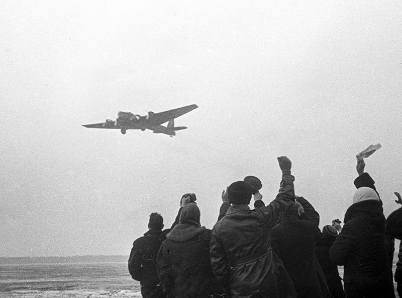 Люди провожают самолет, улетающий на Северный полюс