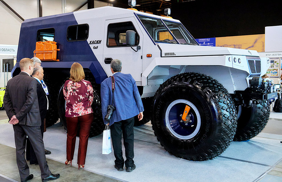 Forum participants near the Trecol-Husky snow and swamp-going vehicle displayed at the 9th International Forum The Arctic: Today and the Future, in St. Petersburg