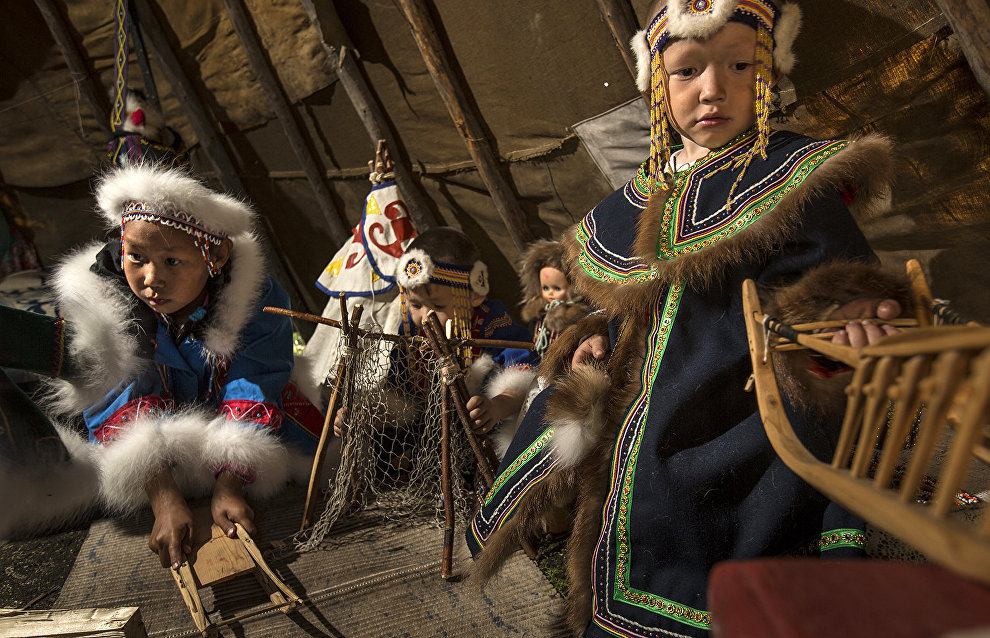 Evenki children play in a balor (small framed or mobile hut) Lake Khantaiskoye, Putorana Plateau