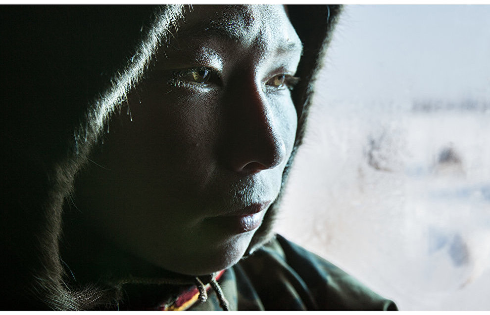 A Nenets reindeer herder from the Palchyn family gets warm in a balok (small frame or mobile hut). The Tukhard tundra, Taimyr