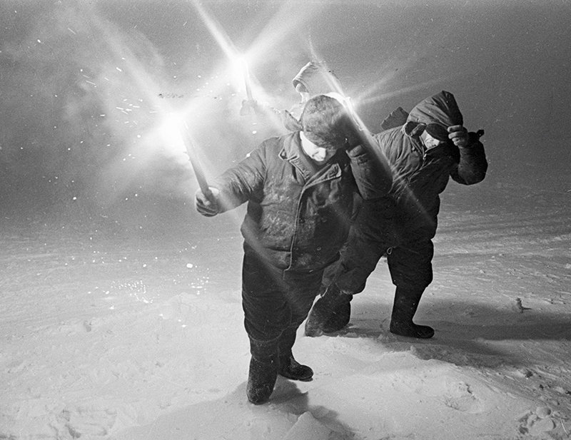 Explorers with lamps in a snowstorm
