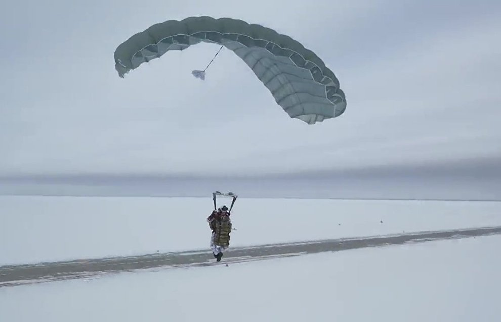 A Russian paratrooper lands after a group jump from 10,000 m of altitude using new parachute systems in extreme Arctic conditions near the Franz Josef Land Archipelago