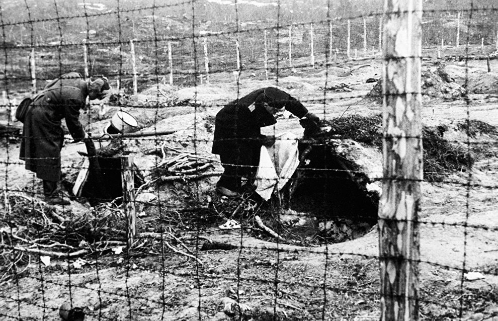 Soldiers examining dugouts where Nazis kept prisoners of a concentration camp in Norway