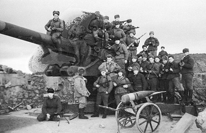 Soviet soldiers sitting on a German gun captured during fighting