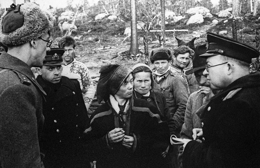 Members of the commission investigating crimes of Nazis during the World War II of 1939-1945 talking to locals in the area of the town of Troms where the concentration camp for Soviet and other prisoners of war was situated